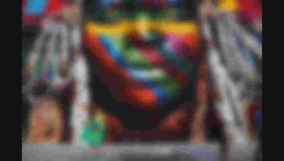 RIO DE JANEIRO, BRAZIL - AUGUST 04:  People walk past a section of a mural depicting an indigenous face created by Brazilian graffiti artist Eduardo Kobra and assistants in the revamped Port District on August 4, 2016 in Rio de Janeiro, Brazil. The 32,000-square-foot mural, titled 'We Are All One', was painted to represent cultural diversity across continents. The start of the Rio 2016 Olympic Games on August 5.  (Photo by Mario Tama/Getty Images)