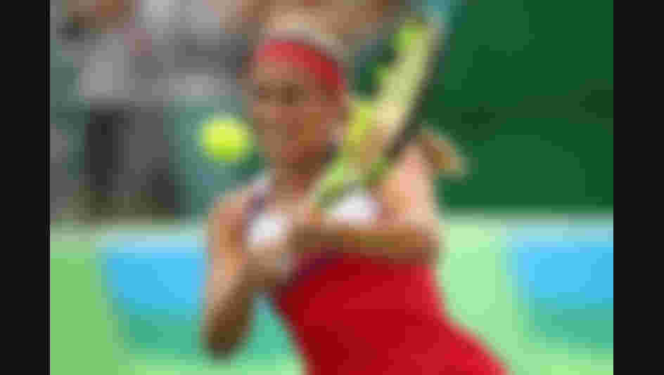 Monica Puig of Puerto Rico plays a backhand during the women's singles quarterfinal match against Laura Siegemund of Germany on Day 6 of the 2016 Rio Olympics.