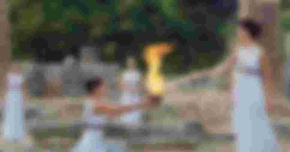 A high priestess passes the Olympic flame at the Temple of Hera during a lighting ceremony in ancient Olympia, Greece.
