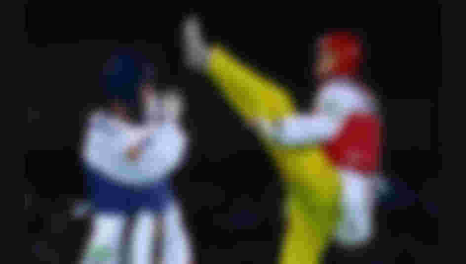 Shuai Zhao of China kicks Jesus Tortosa Cabrera of Spain during the Taekwondo Men's -58kg Round One contest on Day 11 of the Rio 2016 Olympic Games.